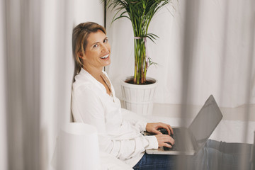 Mature businesswoman working with laptop at home.