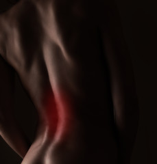 Pain in sporty woman back. Closeup