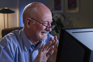 Older man disgusted at information on his computer monitor