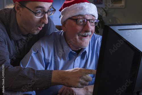 Two men in the holiday spirit in front of computer, horizontal