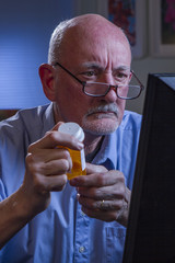 Confused older man refilling prescription online, vertical