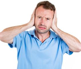 Unhappy, grumpy man covering his ears