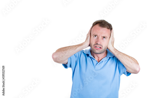 Annoyed man covering ears, having headache from noise