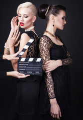 two beautiful girl in retro style with clapperboard