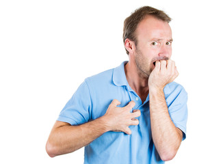 Stressed young man biting his fingernails, looking anxious