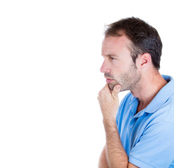 Serious young man daydreaming thinking deeply about past future