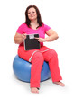 Happy overweight woman with a weighing machine and measure tape.