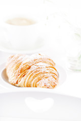 Croissant with coffee, on sunlit breakfast tray