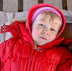 Cute blonde girl toddler in red jacket