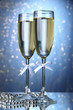 Two glasses of champagne on bright background with lights