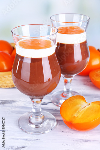 Dessert of chocolate and persimmon on table on light background