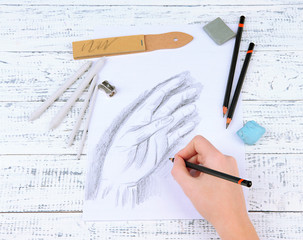 Hand draws a sketch with professional art materials,