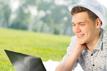 young man working in the park with a laptop