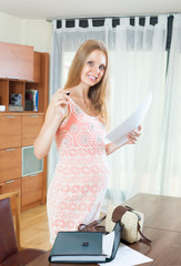 Smiling pregnant woman with documents in home interior