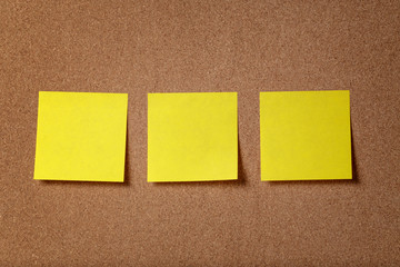 three reminder sticky notes on cork board