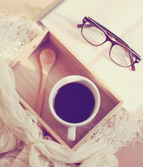 Eyeglasses and book with black coffee on wooden tray, retro filt