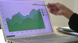 Close up of business woman pointing at charts laptop screen