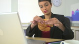 African American business woman eating croissant at desk