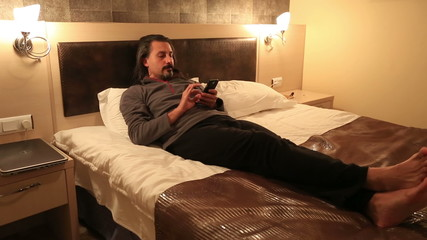 attractive man using smart phone in hotel room