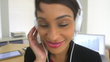 Happy African American business woman listening to music at work