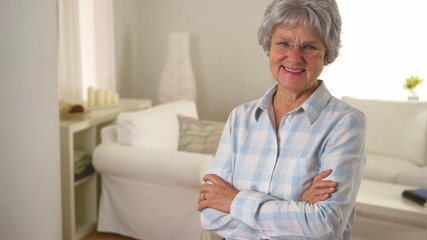 Old woman smiling and standing in living room