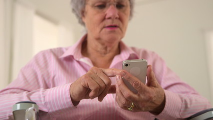 Senior woman using smartphone in wheelchair