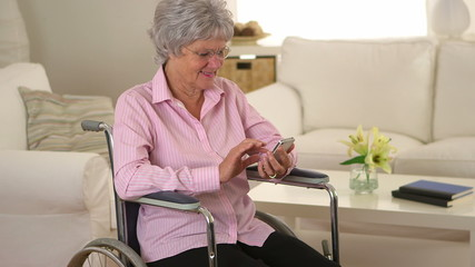 Old woman happily using smartphone