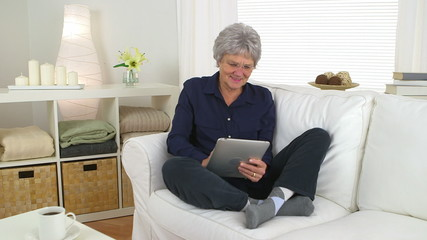 Senior woman using tablet on couch
