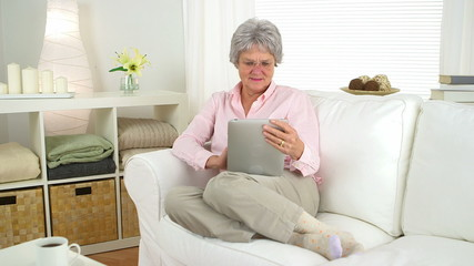 Happy old woman using tablet