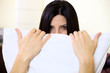 Woman hiding behind pillow amazing eyes