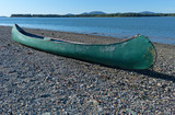 Old green canoe on shore