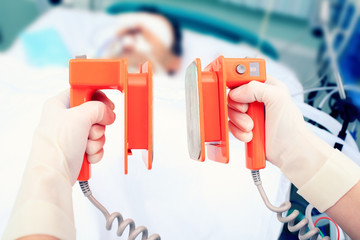 defibrillator electrodes in hands. Work in the ICU