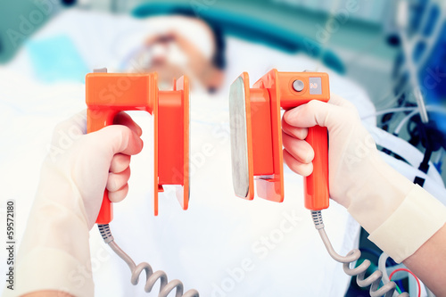 defibrillator electrodes in hands. Work in the ICU