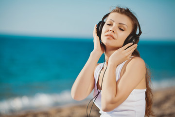 Portrait of a beautiful woman on the beach listening to music