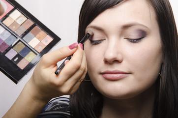 Визажист красит веки девушки, накладывая макияж