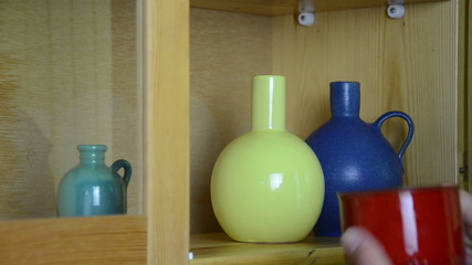 hand take small colorful crockery vases cup from wall rack
