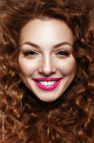 Emotional portrait of a girl with curly red hair (ginger) and fr