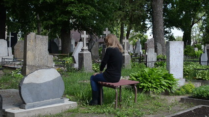 Young woman sit on bench near father grave in cemetery