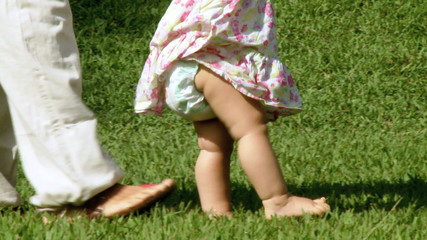 Baby girl first steps helped by mother
