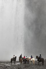 Iceland. South area. Skogafoss waterfall with horses and jockeys