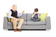 Angry grandfather shouting at his nephew, seated on a sofa