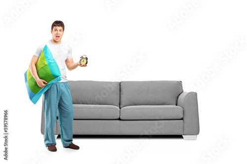 Shocked male in pajamas holding a pillow and alarm clock