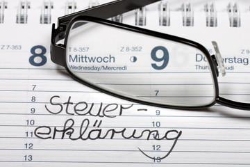 Notiz Steuererklärung mit Brille im aktuellen Kalender