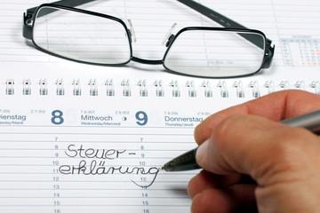 """Hand, Stift, Brille Notiz: """"Steuererklärung"""" in Kalender"""