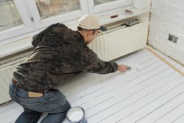 peintre mettant couche de fond primaire sur plancher
