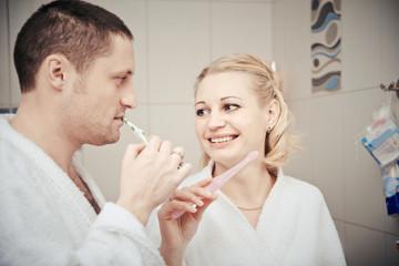 woman and man brushing teeth