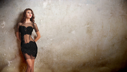 Charming young brunette woman in transparent lace black dress