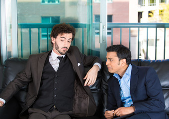 two guys in business suits sitting on couch one complaining