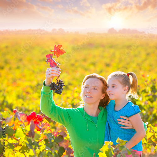 Mother and daughter on autumn vineyard smiling holding grape