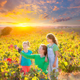 Mother and daughters on autumn vineyard smiling holding grape